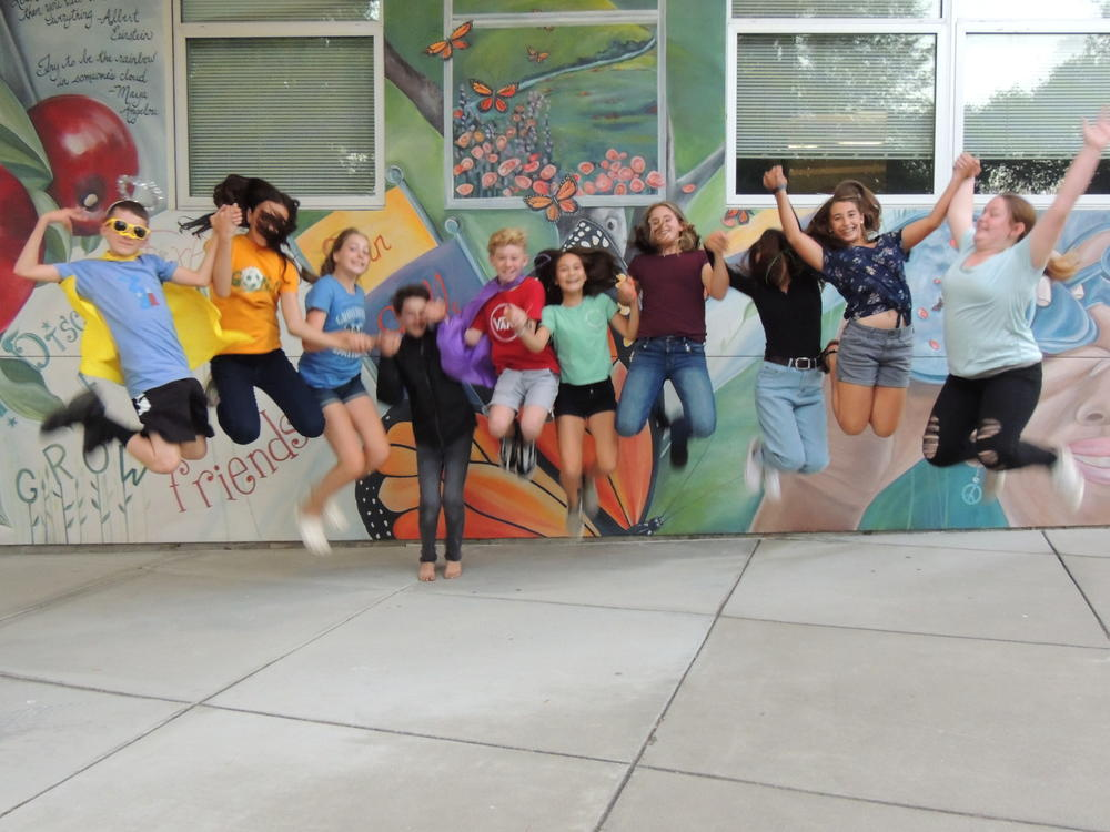 yearbook students jumping in front of mural