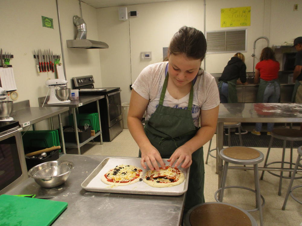 student making pizza in culinary arts