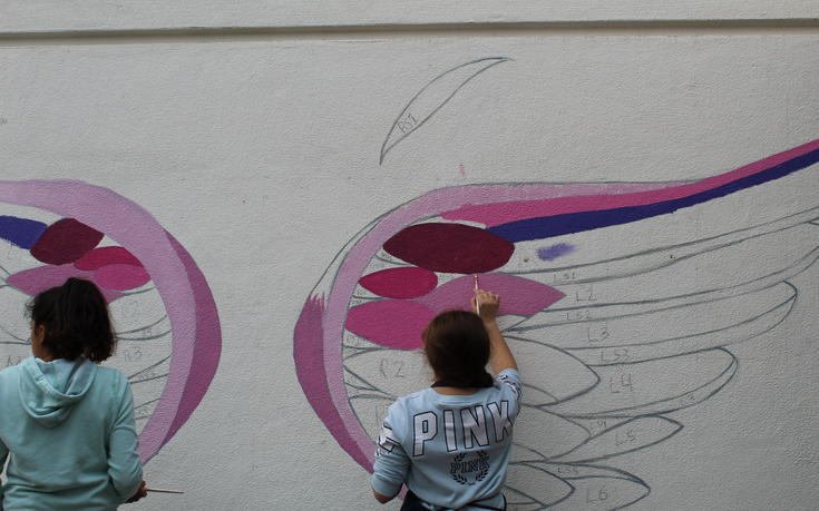 students painting wing mural